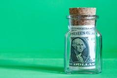 Λογαριασμοί ένας-δολαρίων σε ένα βάζο γυαλιού, σε ένα πράσινο υπόβαθρο Στοκ Εικόνες
