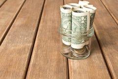 Λογαριασμοί δολαρίων σε ένα βάζο γυαλιού σε έναν ξύλινο πίνακα η έννοια του Π στοκ εικόνες