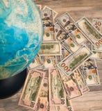Λογαριασμοί εκατό δολαρίων ως υπόβαθρο για τη γεωγραφική σφαίρα Στοκ φωτογραφίες με δικαίωμα ελεύθερης χρήσης