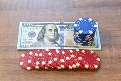 Λογαριασμοί εκατό δολαρίων και τσιπ πόκερ στον ξύλινο πίνακα Στοκ Εικόνες