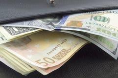 Λογαριασμοί ευρώ και δολαρίων σε ένα μαύρο πορτοφόλι Στοκ εικόνες με δικαίωμα ελεύθερης χρήσης