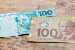 Λογαριασμοί μετρητών από το νόμισμα του Καναδά και της Βραζιλίας Bils στον ξύλινο αγροτικό πίνακα