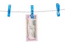 Λογαριασμοί δολαρίων που κρεμούν στο σχοινί που συνδέεται με τις καρφίτσες ενδυμάτων Στοκ Εικόνα