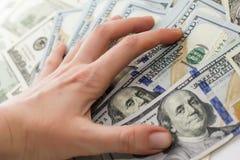 Λογαριασμοί δολαρίων σε διαθεσιμότητα, χέρι με τα χρήματα, δολάριο 100 Στοκ Φωτογραφία
