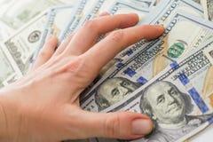 Λογαριασμοί δολαρίων σε διαθεσιμότητα, χέρι με τα χρήματα, δολάριο 100 Στοκ Εικόνες