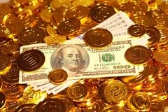 Λογαριασμοί δολαρίων στο χρυσό σωρό νομισμάτων Στοκ Φωτογραφία
