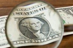 λογαριασμός 1 δολαρίου κάτω από μια ενίσχυση - γυαλί σε έναν ξύλινο πίνακα Ο ομο Στοκ Εικόνες