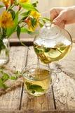 Λογική έκχυση τσαγιού στο διαφανές φλυτζάνι γυαλιού από teapot Στοκ φωτογραφία με δικαίωμα ελεύθερης χρήσης