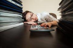Λογιστής κοιμισμένος ενάντια στους μεγάλους σωρούς των εγγράφων Στοκ Φωτογραφίες