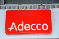 Λογότυπο Adecco σε έναν τοίχο Η ομάδα Adecco, που εδρεύει κοντά στη Ζυρίχη, Ελβετία, είναι η μεγαλύτερη επανδρώνοντας εταιρία στο στοκ εικόνες