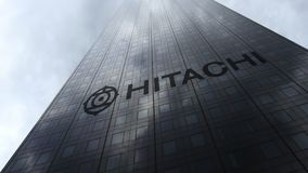 Λογότυπο Hitachi σε μια πρόσοψη ουρανοξυστών που απεικονίζει τα σύννεφα Εκδοτική τρισδιάστατη απόδοση Στοκ φωτογραφία με δικαίωμα ελεύθερης χρήσης