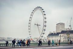 Λονδίνο/Αγγλία - 02 07 2017: Άποψη στο μάτι του Λονδίνου από τη γέφυρα του Γουέστμινστερ με τους τουρίστες που διασχίζουν τη γέφυ Στοκ Φωτογραφία