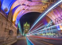 Λονδίνο, Αγγλία - πυροβολισμός νύχτας της παγκοσμίως διάσημης ζωηρόχρωμης γέφυρας πύργων στο Λονδίνο με τα διπλά ελαφριά ίχνη λεω Στοκ Εικόνες