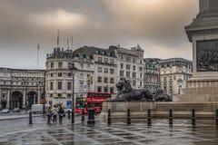Λονδίνο, UK, στις 20 Σεπτεμβρίου 2014, ένα βροχερό πρωί, ένα κόκκινο λεωφορείο, λιοντάρια στη πλατεία Τραφάλγκαρ στοκ φωτογραφία