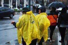 ΛΟΝΔΙΝΟ, ΑΓΓΛΙΑ 11 Μαρτίου 2018 - womn δύο στο παλτό βροχής, κάτω από τη βροχή που περιμένει τα λεωφορεία το πρωί Άποψη οδών στοκ εικόνα