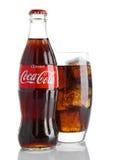 ΛΟΝΔΙΝΟ, UK - 7 ΝΟΕΜΒΡΊΟΥ 2016: Κλασικό μπουκάλι της Coca-Cola με το γυαλί στο άσπρο υπόβαθρο με τα παιχνίδια και το χιόνι Χριστο Στοκ Φωτογραφίες