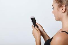 Λοξά πορτρέτο του θηλυκού με το υγιές καθαρό δέρμα που κρατά το κινητό τηλέφωνο στα χέρια με την κενή οθόνη, που διαβάζει τις ειδ στοκ εικόνες