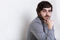 Λοξά πορτρέτο του νέου hipster που έχει τη σκοτεινή γενειάδα με τα μεγάλα σκοτεινά μάτια moustache, τα παχιά φρύδια και το μοντέρ στοκ εικόνες
