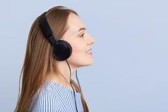 Λοξά το πορτρέτο του λατρευτού νέου θηλυκού με τα ακουστικά ακούει αγαπημένο τραγούδι στο playlist, χρησιμοποιεί την άγνωστη ηλεκ Στοκ Εικόνες
