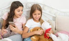 Λοξοτομεί είναι αληθινό Ευτυχή μικρά παιδιά με το κινητό τηλέφωνο Χαρούμενα Χριστούγεννα και χαιρετισμοί καλής χρονιάς Τα μικρά κ στοκ φωτογραφίες