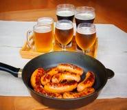 Λουκάνικα και γυαλιά μπύρας στον ξύλινο πίνακα Στοκ Φωτογραφία