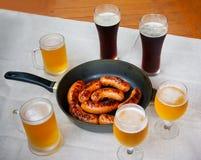Λουκάνικα και γυαλιά μπύρας στον ξύλινο πίνακα Στοκ εικόνες με δικαίωμα ελεύθερης χρήσης