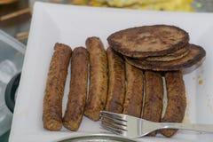 Λουκάνικα και Burgers ακριβώς μαγειρευμένος σε μια σχάρα Στοκ Φωτογραφία