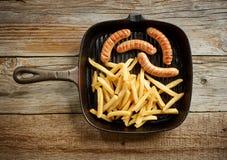 Λουκάνικα κρέατος και τηγανισμένες πατάτες στο τηγάνι χυτοσιδήρου Στοκ Φωτογραφία