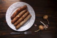 Λουκάνικα κρέατος με το σκόρδο και κρεμμύδια σε ένα πιάτο Στοκ Εικόνες