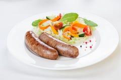 Λουκάνικα με τα λαχανικά σε ένα άσπρο καθαρισμένο εστιατόριο υποβάθρου υπέροχα κομψά Στοκ φωτογραφία με δικαίωμα ελεύθερης χρήσης