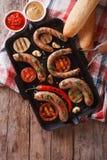 Λουκάνικα με τα λαχανικά σε μια παν σχάρα Κάθετη τοπ άποψη Στοκ Φωτογραφίες