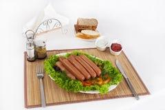 Λουκάνικα που καπνίζονται με τις ντομάτες, τα αγγούρια και τα πράσινα Εξυπηρετημένος με το μαύρο ή άσπρο ψωμί στοκ φωτογραφία με δικαίωμα ελεύθερης χρήσης
