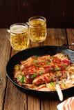Λουκάνικα που τηγανίζονται στο skillet χυτοσιδήρου με δύο κούπες μπύρας Στοκ Εικόνα
