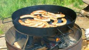 Λουκάνικα που τηγανίζουν στο μεγάλο τηγάνι υπαίθρια απόθεμα βίντεο