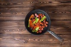 Λουκάνικα στο τηγάνι σχαρών στο ξύλινο υπόβαθρο Στοκ εικόνα με δικαίωμα ελεύθερης χρήσης