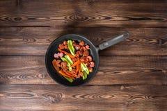 Λουκάνικα στο τηγάνι σχαρών στο ξύλινο υπόβαθρο Στοκ εικόνες με δικαίωμα ελεύθερης χρήσης