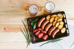 Λουκάνικα χοιρινού κρέατος Griled, ψημένες πατάτες, φρέσκες ντομάτες και κούπες της μπύρας στοκ εικόνα με δικαίωμα ελεύθερης χρήσης