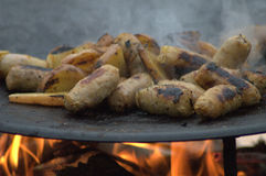Λουκάνικο και μαγείρεμα της Apple πέρα από μια πυρά προσκόπων Στοκ φωτογραφία με δικαίωμα ελεύθερης χρήσης