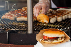 Λουκάνικο και burgers σε ένα τηγάνι σχαρών Στοκ Φωτογραφίες