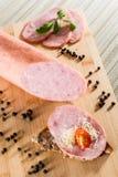 Λουκάνικο με τη φρυγανιά ψωμιού στον ξύλινο τέμνοντα πίνακα σε ελαφρύ Backgr Στοκ εικόνες με δικαίωμα ελεύθερης χρήσης