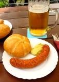 Λουκάνικο με το ψωμί και μουστάρδα στον κήπο μπύρας Στοκ Εικόνες