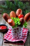 Λουκάνικο σε ένα οβελίδιο σε μια ζύμη καλαμποκιού που τσιγαρίζεται, σπιτικά σκυλιά καλαμποκιού Στοκ εικόνες με δικαίωμα ελεύθερης χρήσης