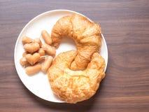 Λουκάνικο Croissant και καρδιών στον ξύλινο πίνακα Στοκ Εικόνες