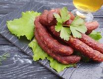 Λουκάνικων μπύρας σαλάτας φύλλων χοιρινού κρέατος πινάκων γαστρονομική κουζίνα γευμάτων τροφίμων οργανική σε έναν ξύλινο πίνακα μ Στοκ φωτογραφία με δικαίωμα ελεύθερης χρήσης