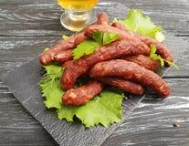 Λουκάνικων σαλάτας φύλλων γαστρονομική κουζίνα γευμάτων πινάκων παραδοσιακή σε έναν ξύλινο πίνακα μαρουλιού υποβάθρου Στοκ φωτογραφία με δικαίωμα ελεύθερης χρήσης