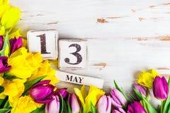 Λουλούδια άνοιξη και ξύλινοι φραγμοί με την ημερομηνία ημέρας μητέρων, στις 13 Μαΐου, Στοκ Φωτογραφίες