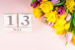 Λουλούδια άνοιξη και ξύλινοι φραγμοί με την ημερομηνία ημέρας μητέρων, στις 13 Μαΐου, Στοκ Φωτογραφία