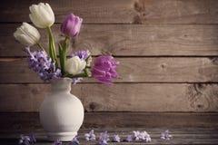 Λουλούδια άνοιξη στο βάζο στο παλαιό ξύλινο υπόβαθρο Στοκ εικόνα με δικαίωμα ελεύθερης χρήσης