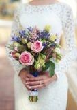 Λουλούδια γαμήλιων ανθοδεσμών στην κομψή νύφη χεριών στοκ φωτογραφία με δικαίωμα ελεύθερης χρήσης