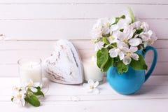 Λουλούδια δέντρων της Apple, διακοσμητικά καρδιά και κεριά στο άσπρο woode Στοκ Εικόνα